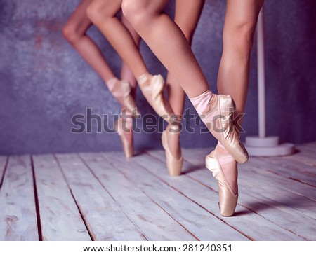The close-up feet of a three young ballerinas in pointe shoes against the background of the wooden floor - stock photo