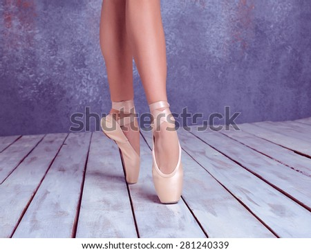 The close-up feet of young ballerina in pointe shoes against the background of the wooden floor - stock photo