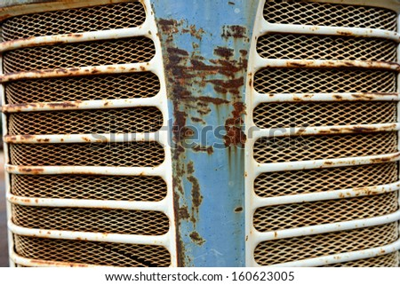 The close up front view of a vintage tractor grill - stock photo