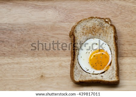 The close up image of fried egg in bread on wooden texture