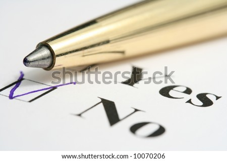 The close-up of a pen and white checklist with a checkboxes with words YES and NO