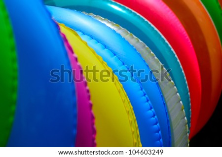 The close up of colorful swimming rings on the beach - stock photo