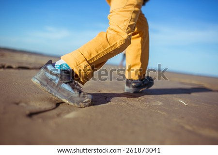 The close-up of the legs of a boy running along the beach. Clothes: yellow pants, trainers. - stock photo