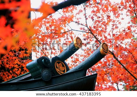 The close-up picture of the eave of an ancient Japanese temple with many red autumn maple leaves. - stock photo