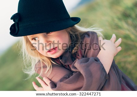 The close-up portrait of a little girl in a hat over green grass background - stock photo