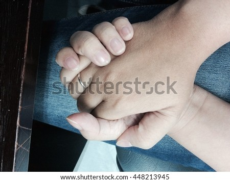 The close up shot of couple hand holding together under table in vintage concept of  secret love, care, encourage and relationship - stock photo