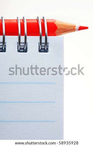 The closeup of notepad and red pencil on white background - stock photo