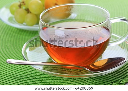 The closeup of the cup of tea with a silver spoon - stock photo