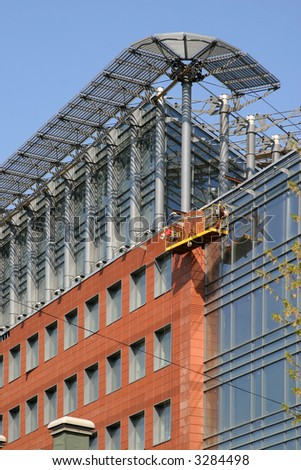 The closing stage of construction the business center, a building from glass and metal on a background of the blue sky