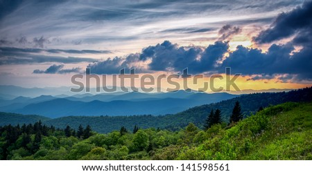 The clouds are rising as the sun is setting on the Blue Ridge Parkway near Asheville and Waynesville, North Carolina. - stock photo