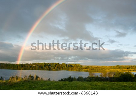 The cloudy sky and autumn rainbow above lake