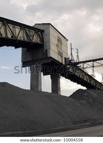 The coal mine, plies of coal and the cloudy sky - stock photo