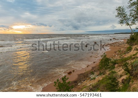 The coast of the Baltic Sea covered with stones in beams of the sunset sun