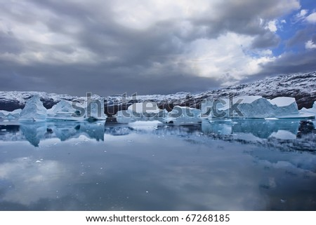 the coasts of greenland with giant floating icebergs and mountains - stock photo