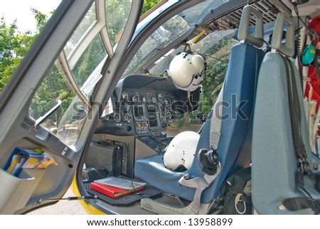 The cockpit of a rescue helicopter with pilot helmets.