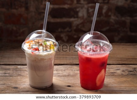 The cocktails in a plastic cup with a straw - stock photo