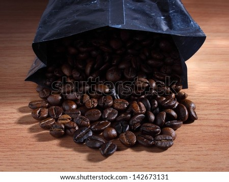 the coffee beans fall from the bag - stock photo