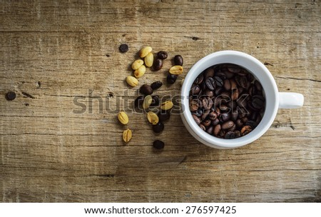 The coffee beans in a cup on a wooden floor. - stock photo