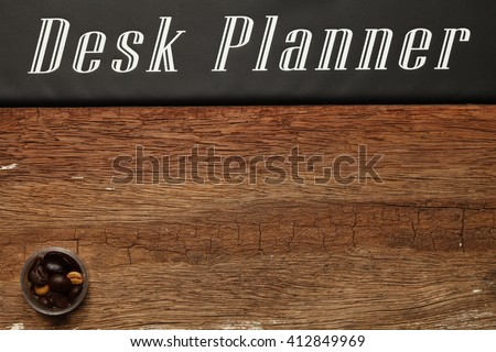 The coffee beans put on brown color hardwood background represent the coffee and raw food material concept related idea.
