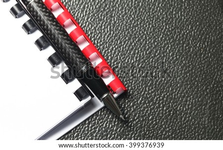 The coil book binding spine on document cover and pen represent the book and paper binding concept related idea.