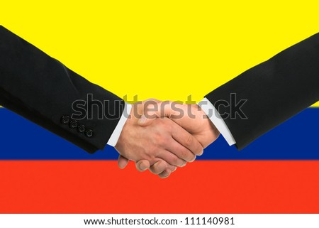 The Colombian flag and business handshake - stock photo