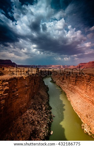 The Colorado River runs beneath the Navajo Bridge in Arizona beneath stormy and cloudy skies - stock photo