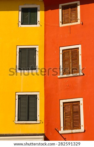 The colored wall and the windows with shutters, mediterranean architecture. - stock photo