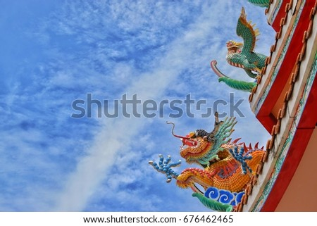 The colorful dragons are on the the Chinese roof with the blue sky background