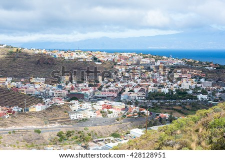 The colorful houses of San Sebastian de La Gomera on the Canary island La Gomera. San Sebastian is the capital of the Island. In the background, the island Tenerife - stock photo