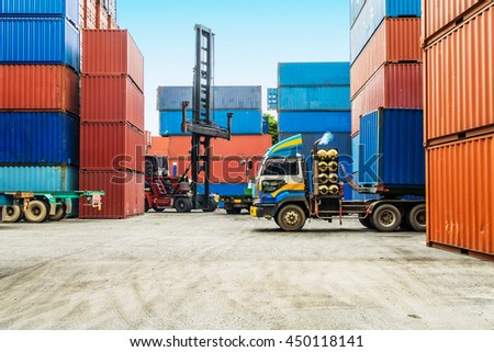 The colorful steel containers and the truck in the logistic hub on the blue sky background