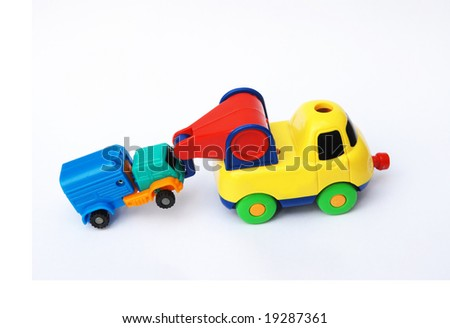 The colorful toy trail truck dragging a van. - stock photo