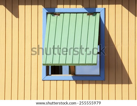 The colorful window of a wooden structure built on Half Moon Cay beach (The Bahamas). - stock photo