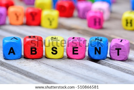The colorful word Absent on wooden table