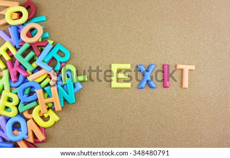 """The colorful word """"EXIT"""" next to a pile of other letters over the brown board surface composition. - stock photo"""