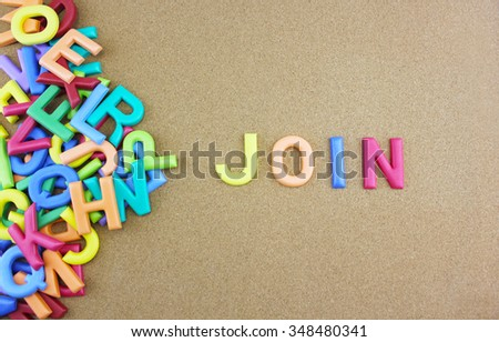 """The colorful word """"JOIN"""" next to a pile of other letters over the brown board surface composition. - stock photo"""