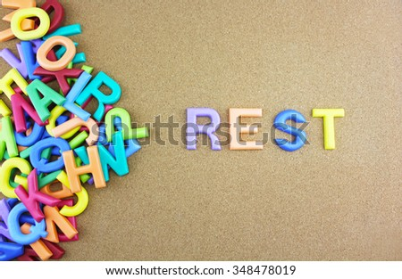 """The colorful word """"REST"""" next to a pile of other letters over the brown board surface composition. - stock photo"""