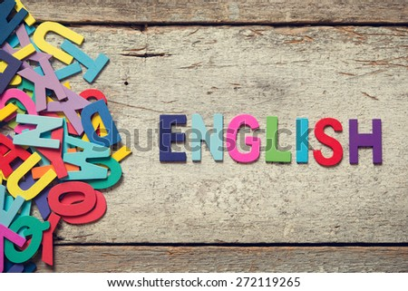 "The colorful words ""ENGLISH"" made with wooden letters next to a pile of other letters over old wooden board. - stock photo"