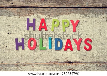 "The colorful words ""HAPPY HOLIDAYS"" made with wooden letters on wood board. - stock photo"