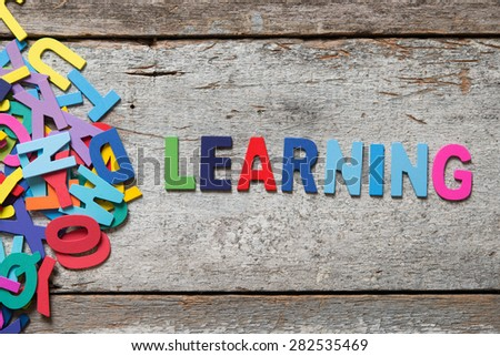 "The colorful words ""LEARNING"" made with wooden letters next to a pile of other letters over old wooden board. - stock photo"