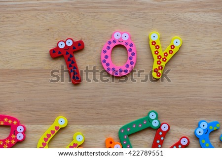 """The colorful words """" toy """" made with wooden letters next to a pile of other letters over old wooden board. - stock photo"""