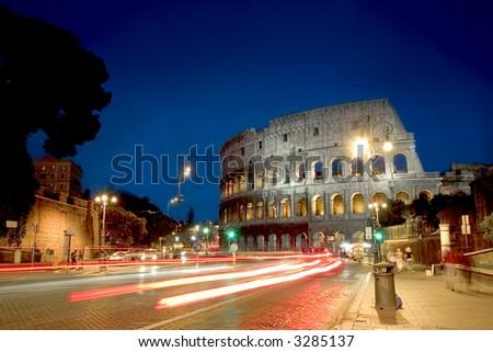 The Coloseum of Rome seen at night along Via del Fori Imperiali - stock photo