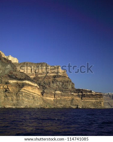The colossal volcanic cliffs of Santorini Greece - stock photo