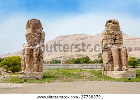 The Colossi of Memnon are two giant stone statues of Pharaoh Amenhotep III. Luxor, West Bank, Egypt - stock photo