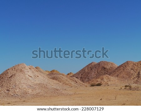 The colourful earth hills around the Australian outback opal mining town of Coober Pedy in South Australia - stock photo