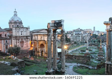 The columns of the Temple of Saturn, Arch of Septimius Severus and the medieval church in the Roman Forum, Rome, Italy - stock photo