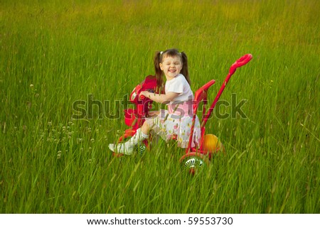 The comical child goes across the field on a bicycle and grimace