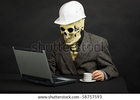 The comical construction superintendent in a helmet and a skeleton mask works with the computer - stock photo