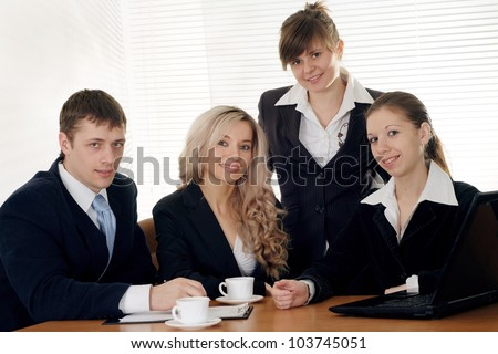 The company of four joy caucasian businessman working at a table on a white background - stock photo