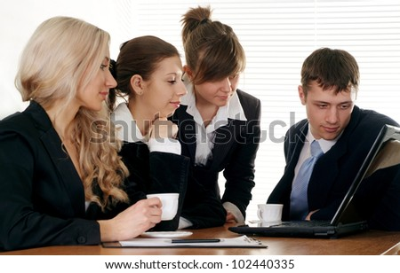 The company of four pretty businessman working at a table on a white background - stock photo