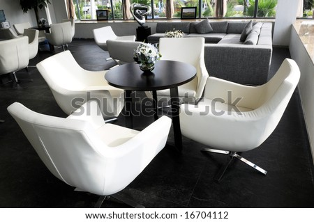 The company parlor room with white swivel leather chairs and round tea table.